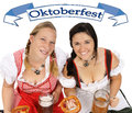 Two pretty women in dirndl with beer mug and banner Royalty Free Stock Photography