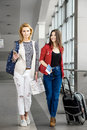 Two pretty women are on the terminal with a suitcase, a backpack. Mother and daughter go on holiday Royalty Free Stock Photo