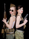 Two pretty young women in  military uniform with guns Royalty Free Stock Photo