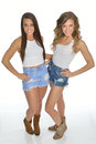 Two pretty young women pose in country western outfits Royalty Free Stock Photo