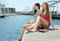 Two pretty young women sitting on the berth at summer day Royalty Free Stock Photos