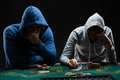 Two professional poker players sitting at a poker table on black background trying to hide his expressions Stock Image