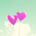 Two purple heart shaped balloons over blue sky Royalty Free Stock Images