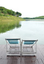 Two recline chairs on dock facing a green lake in thailand Stock Photography