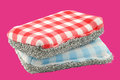 Two red and blue checkered abrasive pads on a pink background Royalty Free Stock Images