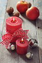 Two red candles with christmas decor on wooden background Stock Photo