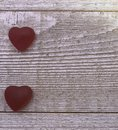 Two red candy hearts on a gray board background