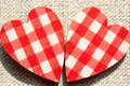 Two red checkered love hearts on burlap background rough closeup Stock Photo