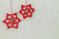 Two red crochet christmas stars with golden button Royalty Free Stock Photo