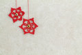 Two red crochet christmas stars on sponged background
