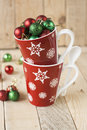 Two red cups with snowflakes and ornaments on a Christmas tree Royalty Free Stock Photo