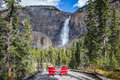 Two red deckchairs for tourists opposite waterfall. Royalty Free Stock Photo