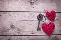 Two red decorative  hearts and key on vintage wooden background Royalty Free Stock Photo