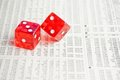 Two red dice on the financial newspaper Stock Photos