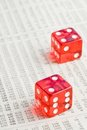 Two red dice on the financial newspaper Stock Images