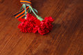 Two red flower Symbols of Victory in Great Patriotic War on wooden Royalty Free Stock Photo