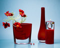 Two red glass vases and candle on blue Stock Image
