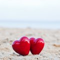 Two red hearts on the beach symbolizing love valentine s day romantic couple calm ocean in background Stock Photos