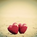 Two red hearts on the beach symbolizing love valentine s day romantic couple calm ocean in background vintage retro style Royalty Free Stock Photography