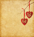 Two red hearts hanging on a branch over the paper background Royalty Free Stock Photography