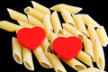 Two red love hearts on fresh pasta with black background Royalty Free Stock Images