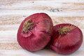 Two red onions on the white painted wooden background. Royalty Free Stock Photo