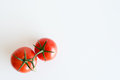 Two red tomatoes on white table from above Royalty Free Stock Photo