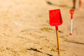 Two red toy shovels in sand on beach Royalty Free Stock Photo