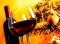 Two red wine glasses near bottle against christmas tree background Royalty Free Stock Photo
