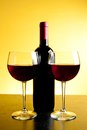 Two red wine glasses near bottle on golden background and wood table Stock Photo