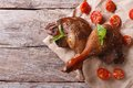Two roasted duck legs with basil and tomatoes closeup  an table Royalty Free Stock Photo