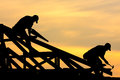 Two roofer working on roof structure sunflare Stock Image