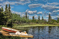 Two rowboats on a blue lake old sit the edge of calm surrounded by pine trees and mountains all under sky with puffy white Royalty Free Stock Images