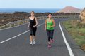 Two runner women running on mountain road in beautiful nature volcanic landscape canary islands Stock Image