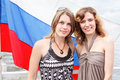 Two Russian women under flag of Russia Stock Image