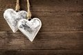 Two rustic metal heart ornaments hanging on wood Royalty Free Stock Photo