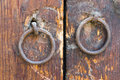 Two rusty iron ring door knobs over an old wooden door Royalty Free Stock Photo
