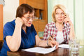 Two sad mature women reading documents at table Royalty Free Stock Photo