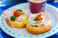 Two sandwiches with ham, parsley and cherry lying on a plate in a cafe