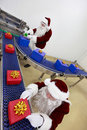 Two santa clauses working at production line Royalty Free Stock Image