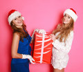 Two santa girlfriends with a red gift in studio on pink background Royalty Free Stock Images