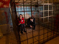 Two scared Halloween victims imprisoned in a metal cage