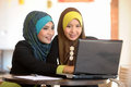 Two scarf girl use laptop cafe Royalty Free Stock Photography