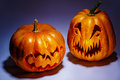 Two scary Halloween pumpkins with shadows on a coloured backgrou Royalty Free Stock Photo