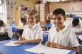 Two schoolboys in a primary school class, looking to camera