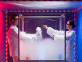 Two scientists experimenting with steamy reactions a men and a woman mixing chemicals in a sterile chamber labeled as bio Royalty Free Stock Photography