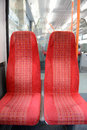 Two seats on a commuter train closeup of red in the interior carriage of Royalty Free Stock Photo