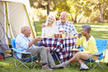 Two senior couples enjoying camping holiday in countryside laughing Royalty Free Stock Photography