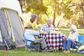 Two senior couples enjoying camping holiday in countryside smiling Royalty Free Stock Photos