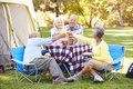 Two senior couples enjoying camping holiday in countryside smiling Stock Photos